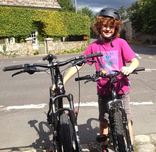 small child wearing pink t-shrt hold his bike and a larger one