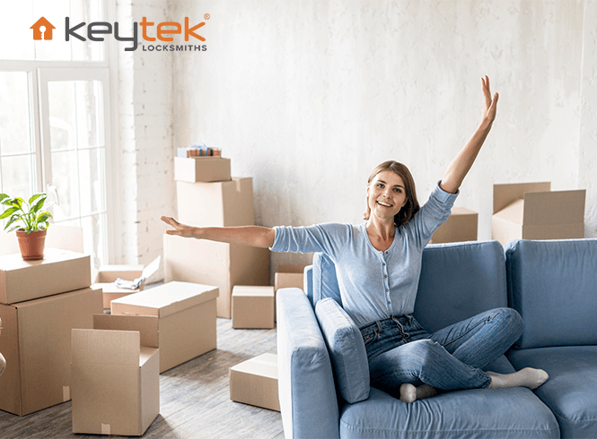 happy women sat on sofa surrounded by moving boxes