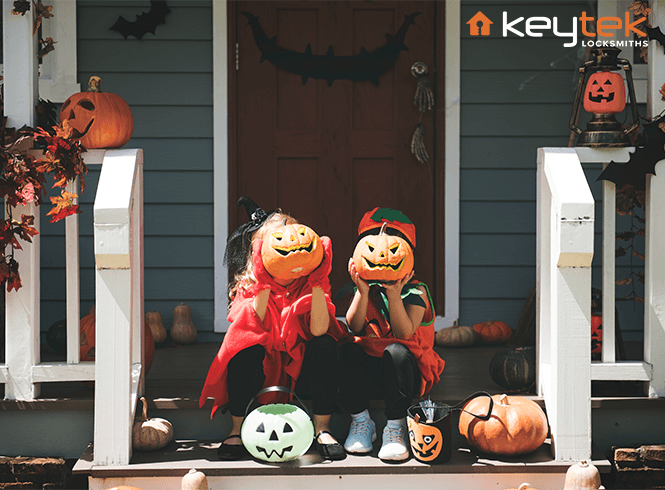 Children dressed up for halloween sat on porch with pumpkins