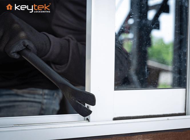 burglar entering upvc window using crowbar