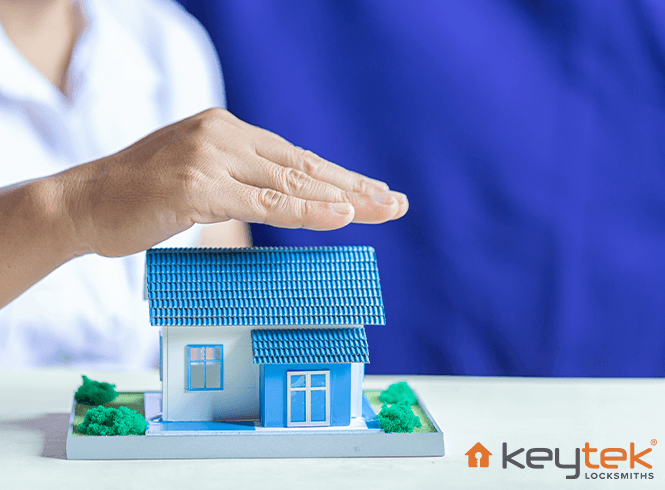 Blue model house covered by a hand