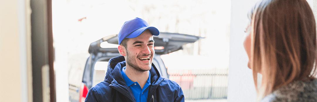 Smiling Locksmith greeting customer at the door