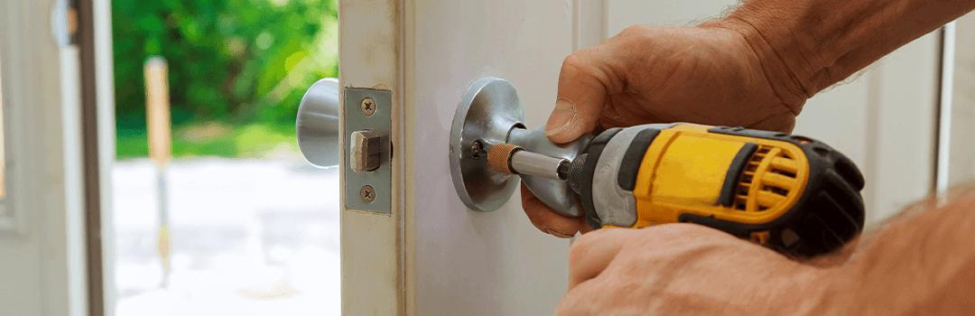 Locksmith working on doorknob with a screwdriver
