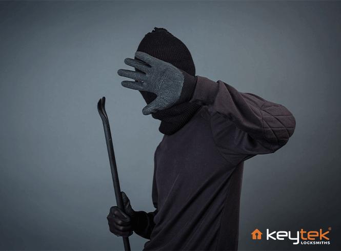 burglar holding a crow bar wearing dark grey and a black hat