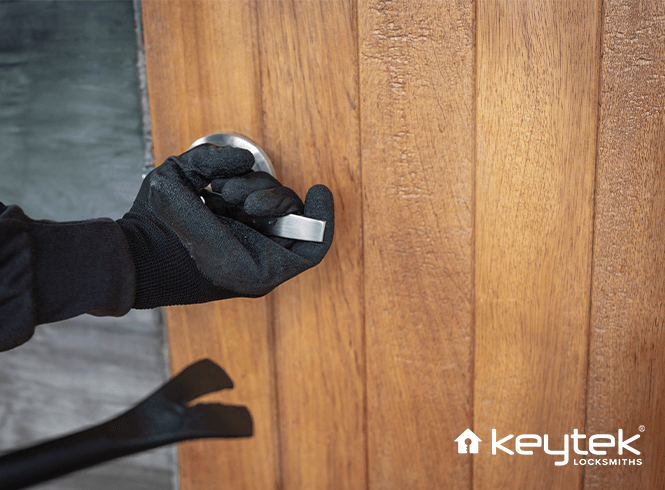 Glove covered hand opening a wood covered door with a crowbar