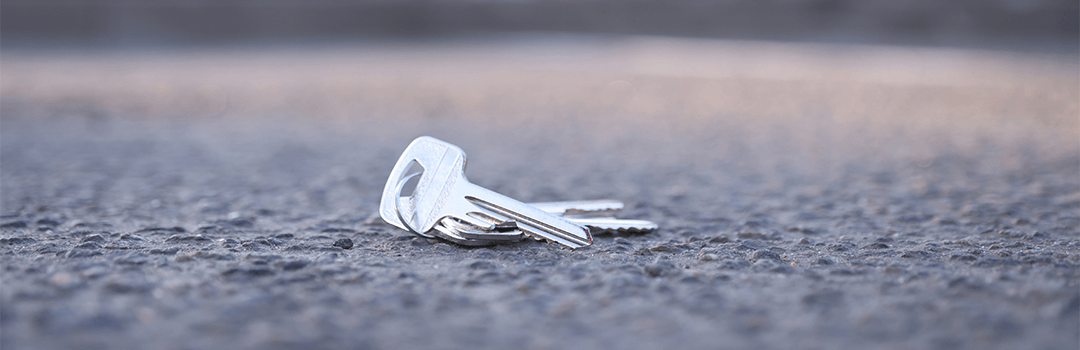 silver keys laying on concrete