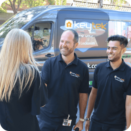 two keyetk locksmith shake hands with a customer with keytek van in the background