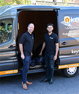 two keytek locksmiths standing outside work van