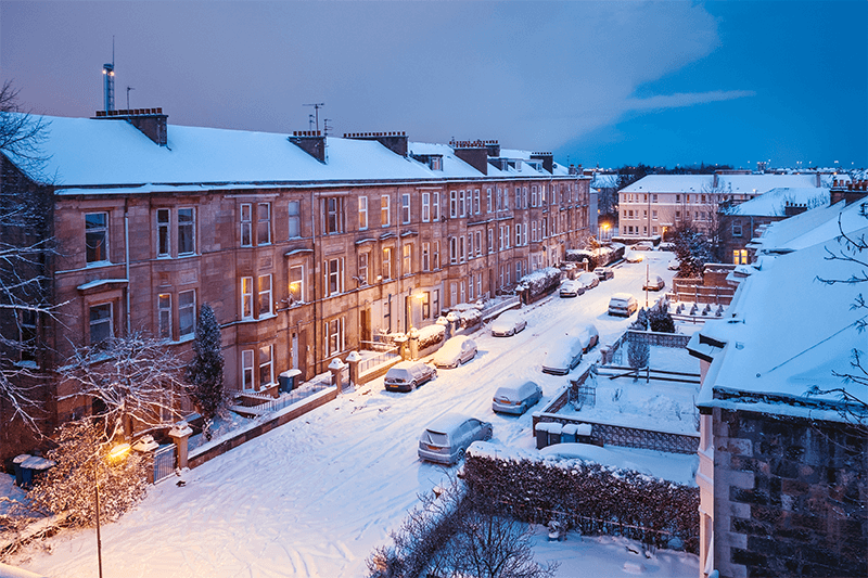 Snow covered Glasgow residential Street at night
