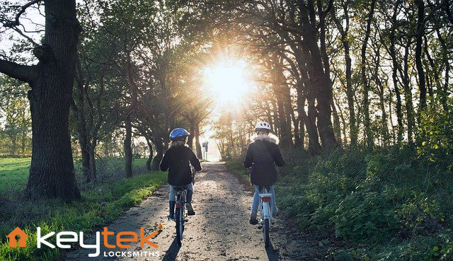 2 girls riding bike with helmets at sunset